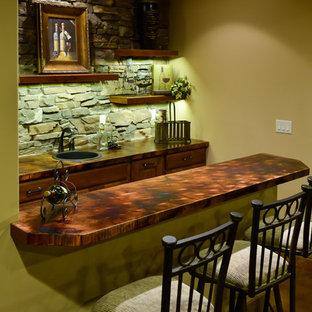 デンバーの中くらいのラスティックスタイルのおしゃれな着席型バー (ll型、ドロップインシンク、レイズドパネル扉のキャビネット、濃色木目調キャビネット、銅製カウンター、マルチカラーのキッチンパネル、石タイルのキッチンパネル、コンクリートの床、茶色い床) の写真
