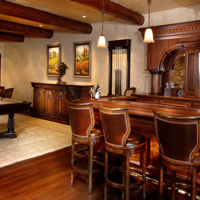 Example of a large mountain style dark wood floor and brown floor seated home bar design in Denver with an undermount sink, raised-panel cabinets, dark wood cabinets, copper countertops and mirror backsplash