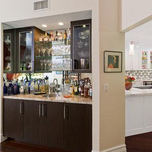 Immagine di un piccolo angolo bar con lavandino classico con lavello sottopiano, ante di vetro e ante in legno bruno