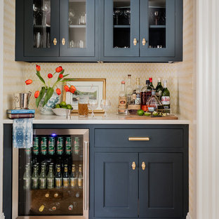 Inspiration for a traditional single-wall home bar in Boston with no sink, glass-front cabinets, blue cabinets, multi-coloured floors and white worktops.