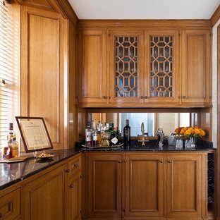 Inspiration for a timeless l-shaped medium tone wood floor wet bar remodel in New York with an undermount sink, furniture-like cabinets, medium tone wood cabinets and mirror backsplash