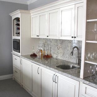Ispirazione per un angolo bar con lavandino tradizionale con lavello sottopiano, ante con bugna sagomata, ante beige, top in granito, paraspruzzi grigio, paraspruzzi in lastra di pietra e moquette