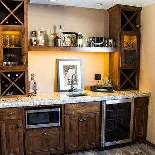 ミネアポリスの中くらいのトラディショナルスタイルのおしゃれなウェット バー (I型、ガラス扉のキャビネット、中間色木目調キャビネット、御影石カウンター、茶色いキッチンパネル、セラミックタイルの床、アンダーカウンターシンク) の写真