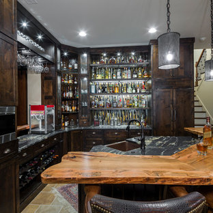 Example of a mountain style l-shaped beige floor wet bar design in Charlotte with an undermount sink, shaker cabinets, dark wood cabinets, wood countertops and brown countertops