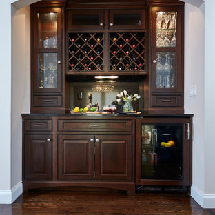 Photo of a traditional home bar in New York with raised-panel cabinets, dark wood cabinets, dark hardwood flooring and brown floors.