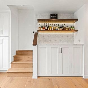 ロサンゼルスの中くらいのトランジショナルスタイルのおしゃれなホームバー (シェーカースタイル扉のキャビネット、白いキャビネット、クオーツストーンカウンター、白いキッチンパネル、セメントタイルのキッチンパネル、淡色無垢フローリング、茶色い床、白いキッチンカウンター) の写真