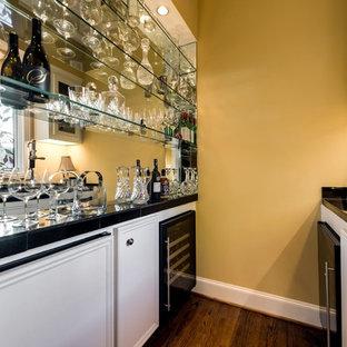 ダラスの小さいトラディショナルスタイルのおしゃれなウェット バー (ll型、アンダーカウンターシンク、レイズドパネル扉のキャビネット、白いキャビネット、タイルカウンター、ミラータイルのキッチンパネル、無垢フローリング) の写真