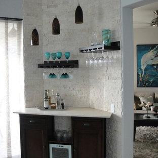 マイアミの小さいビーチスタイルのおしゃれなホームバー (I型、シンクなし、落し込みパネル扉のキャビネット、黒いキャビネット、ライムストーンカウンター、白いキッチンパネル、レンガのキッチンパネル、セラミックタイルの床) の写真