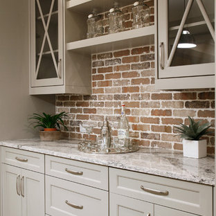 This is an example of a large contemporary single-wall home bar in Atlanta with glass-front cabinets, grey cabinets, marble worktops, multi-coloured splashback, light hardwood flooring and brick splashback.