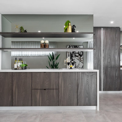 Example of a trendy single-wall concrete floor and gray floor wet bar design in Perth with flat-panel cabinets, dark wood cabinets, mirror backsplash and white countertops