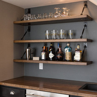 Large classic single-wall wet bar in Other with a built-in sink, recessed-panel cabinets, wood worktops, grey splashback and brown worktops.