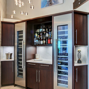 Inspiration for a medium sized contemporary l-shaped wet bar in Tampa with flat-panel cabinets, dark wood cabinets, marble worktops, white splashback, marble splashback, light hardwood flooring, beige floors and white worktops.