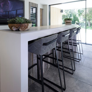 Inspiration for a medium sized contemporary galley wet bar in Cheshire with a built-in sink, flat-panel cabinets, medium wood cabinets, concrete worktops, white splashback, ceramic splashback, ceramic flooring and grey floors.