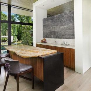 アトランタの広いコンテンポラリースタイルのおしゃれな着席型バー (I型、一体型シンク、フラットパネル扉のキャビネット、中間色木目調キャビネット、オニキスカウンター、グレーのキッチンパネル、石スラブのキッチンパネル、淡色無垢フローリング、ベージュの床、マルチカラーのキッチンカウンター) の写真