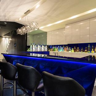 Inredning av en modern stor blå u-formad blått hemmabar med stolar, med släta luckor, vita skåp och blått stänkskydd