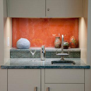 Large contemporary u-shaped home bar in Boston with a submerged sink, flat-panel cabinets, beige cabinets, granite worktops, orange splashback and glass sheet splashback.