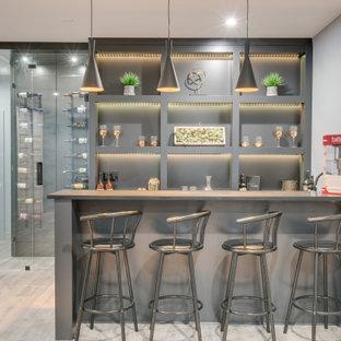 バンクーバーの中くらいのコンテンポラリースタイルのおしゃれな着席型バー (I型、アンダーカウンターシンク、オープンシェルフ、グレーのキャビネット、ラミネートの床、グレーの床) の写真