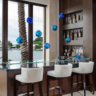 Réalisation d'un bar de salon design en L avec des tabourets, des portes de placard en bois sombre, un plan de travail en verre et un plan de travail bleu.
