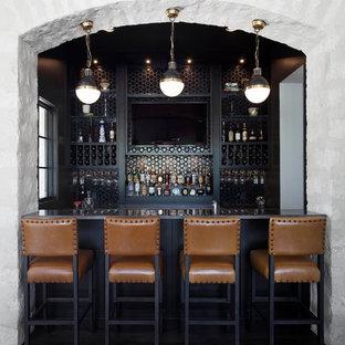 Cette image montre un bar de salon parallèle traditionnel de taille moyenne avec un bar à boissons, un évier encastré, des portes de placard noires, un plan de travail en quartz, une crédence noire, une crédence en carreau de verre, un sol marron, un plan de travail marron et un sol en bois foncé.
