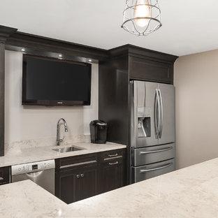 シカゴの広いトランジショナルスタイルのおしゃれなウェット バー (L型、アンダーカウンターシンク、シェーカースタイル扉のキャビネット、黒いキャビネット、クオーツストーンカウンター、クッションフロア、茶色い床、ベージュのキッチンカウンター) の写真