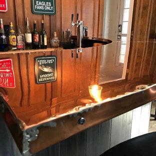 Esempio di un piccolo bancone bar industriale con nessun'anta, ante nere, top in rame, paraspruzzi in legno, pavimento in legno massello medio e top arancione