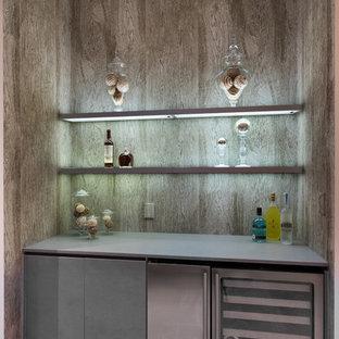 Foto di un piccolo angolo bar con lavandino design con ante lisce, ante grigie, top in quarzo composito e pavimento in travertino