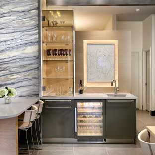 Seated home bar - mid-sized contemporary l-shaped slate floor seated home bar idea in Orange County with an undermount sink, flat-panel cabinets, black cabinets, marble countertops, stone slab backsplash and beige backsplash
