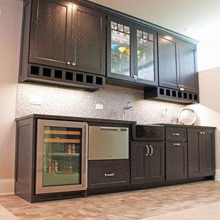 シカゴの中くらいのおしゃれなウェット バー (濃色木目調キャビネット、木材カウンター、グレーのキッチンパネル、モザイクタイルのキッチンパネル、ラミネートの床、茶色い床、茶色いキッチンカウンター、I型、アンダーカウンターシンク、落し込みパネル扉のキャビネット) の写真