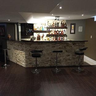 Idee per un grande bancone bar design con parquet scuro, pavimento marrone, nessun lavello, nessun'anta, ante in legno bruno, top in saponaria e top nero
