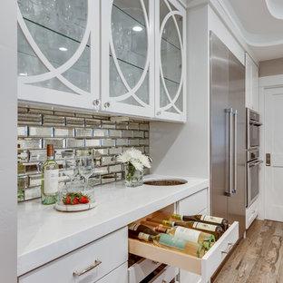 Ispirazione per un angolo bar con lavandino tradizionale di medie dimensioni con lavello sottopiano, ante lisce, ante bianche, top in superficie solida, paraspruzzi a specchio, pavimento in legno massello medio, pavimento marrone e top bianco