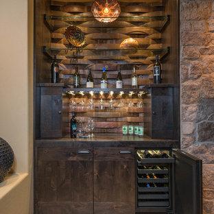 フェニックスの小さいサンタフェスタイルのおしゃれなホームバー (I型、シンクなし、茶色いキッチンパネル、フラットパネル扉のキャビネット) の写真