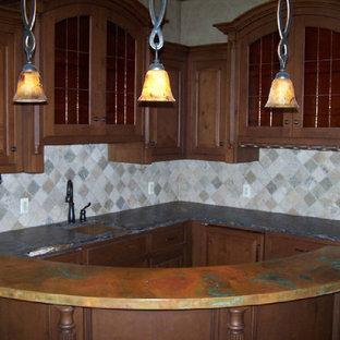 Cette photo montre une grand cuisine chic en U avec un évier encastré, un placard à porte vitrée, des portes de placard en bois sombre et un plan de travail en cuivre.