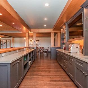 ボストンの広いおしゃれなウェット バー (ll型、シェーカースタイル扉のキャビネット、グレーのキャビネット、無垢フローリング、コンクリートカウンター、木材のキッチンパネル、茶色い床、グレーのキッチンカウンター) の写真