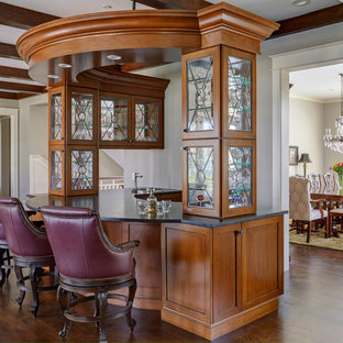 Inspiration for a large timeless galley dark wood floor and brown floor wet bar remodel in Chicago with a drop-in sink, furniture-like cabinets, medium tone wood cabinets, granite countertops and black countertops
