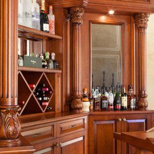 Idee per un bancone bar classico di medie dimensioni con nessun lavello, ante con bugna sagomata, ante in legno scuro, top in legno, pavimento in laminato e pavimento giallo