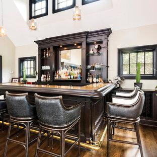 Esempio di un armadio bar tradizionale di medie dimensioni con lavello sottopiano, ante con bugna sagomata, ante in legno bruno, top in granito, paraspruzzi a specchio, pavimento in legno verniciato, pavimento marrone e top giallo