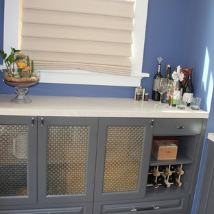 Small elegant l-shaped wet bar photo in Los Angeles with raised-panel cabinets, solid surface countertops, an undermount sink and gray cabinets