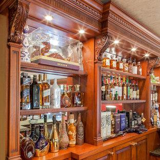 Esempio di un angolo bar con lavandino tradizionale di medie dimensioni con nessun lavello, ante con bugna sagomata, ante in legno scuro, top in granito, paraspruzzi grigio, paraspruzzi a specchio, pavimento in laminato, pavimento giallo e top grigio