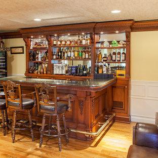 ニューヨークの中くらいのトラディショナルスタイルのおしゃれなウェット バー (コの字型、シンクなし、レイズドパネル扉のキャビネット、中間色木目調キャビネット、御影石カウンター、グレーのキッチンパネル、ミラータイルのキッチンパネル、ラミネートの床、黄色い床、グレーのキッチンカウンター) の写真