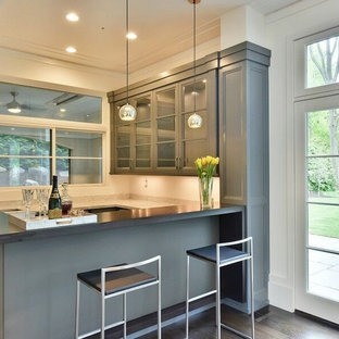 Photo of a medium sized traditional u-shaped breakfast bar in New York with glass-front cabinets, grey cabinets, marble worktops, dark hardwood flooring and brown floors.