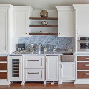 ニューヨークの中くらいのコンテンポラリースタイルのおしゃれな着席型バー (I型、アンダーカウンターシンク、レイズドパネル扉のキャビネット、白いキャビネット、大理石カウンター、グレーのキッチンパネル、大理石のキッチンパネル、ラミネートの床、茶色い床、グレーのキッチンカウンター) の写真
