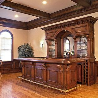 Immagine di un grande bancone bar con ante con bugna sagomata, ante in legno scuro, top in legno, nessun lavello, paraspruzzi grigio, paraspruzzi a specchio, pavimento in laminato, pavimento giallo e top marrone
