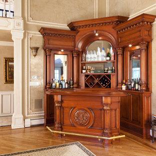 Esempio di un bancone bar di medie dimensioni con ante con bugna sagomata, ante in legno scuro, top in legno, nessun lavello, paraspruzzi a specchio, pavimento in laminato, pavimento giallo e top giallo