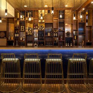 Foto di un grande bancone bar contemporaneo con nessun'anta, ante in legno bruno, pavimento in legno massello medio, top in legno, paraspruzzi marrone, paraspruzzi in legno e pavimento marrone
