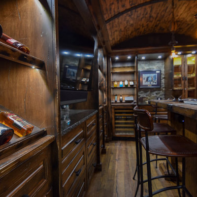 Inspiration for a large rustic u-shaped medium tone wood floor and brown floor seated home bar remodel in Edmonton with raised-panel cabinets, dark wood cabinets, wood countertops, brown backsplash and wood backsplash