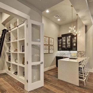 オースティンの中くらいのトランジショナルスタイルのおしゃれなウェット バー (ガラス扉のキャビネット、濃色木目調キャビネット、L型、アンダーカウンターシンク、クオーツストーンカウンター、グレーのキッチンパネル、石タイルのキッチンパネル、磁器タイルの床、茶色い床、白いキッチンカウンター) の写真
