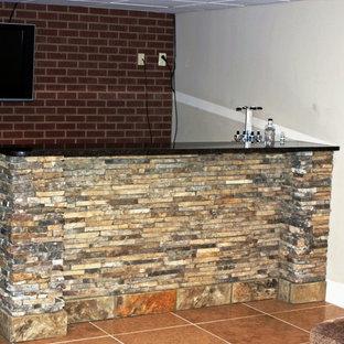 Idee per un piccolo angolo bar con lavandino industriale con lavello da incasso, ante con riquadro incassato, top in granito, paraspruzzi rosso, paraspruzzi in mattoni, pavimento in gres porcellanato, pavimento arancione e top nero