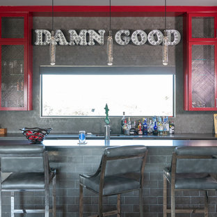 Idée de décoration pour un bar de salon parallèle urbain de taille moyenne avec un évier encastré, des portes de placard rouges, un plan de travail en quartz modifié, une crédence grise, une crédence en carreau de céramique, un sol en bois brun, un sol gris, un plan de travail noir, des tabourets et un placard à porte shaker.