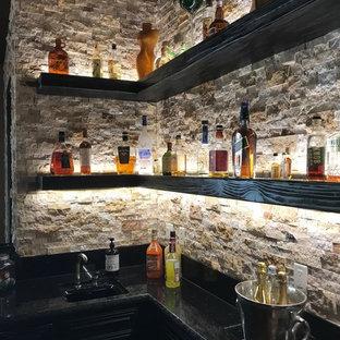 Idee per un bancone bar industriale di medie dimensioni con paraspruzzi marrone, paraspruzzi con piastrelle in pietra, pavimento in cemento, pavimento marrone e top nero