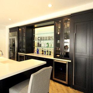 Idées déco pour un grand bar de salon linéaire moderne avec des tabourets, un évier encastré, un placard à porte shaker, des portes de placard en bois sombre, un plan de travail en quartz modifié, une crédence blanche, une crédence en feuille de verre, un sol en bois brun et un sol marron.